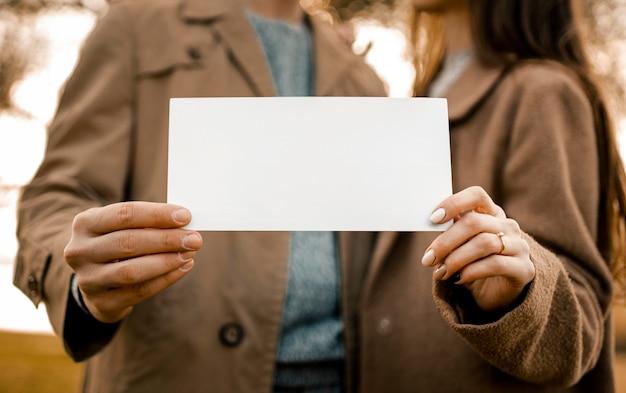Mani del primo piano che tengono carta Foto Gratuite