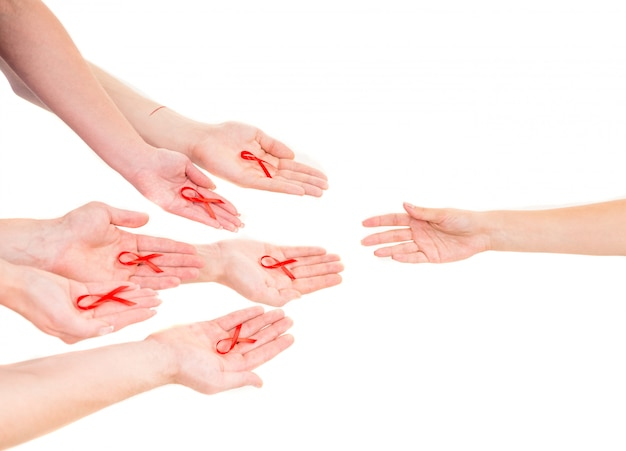 Close-up of hands holding red ribbons on white. Premium Photo