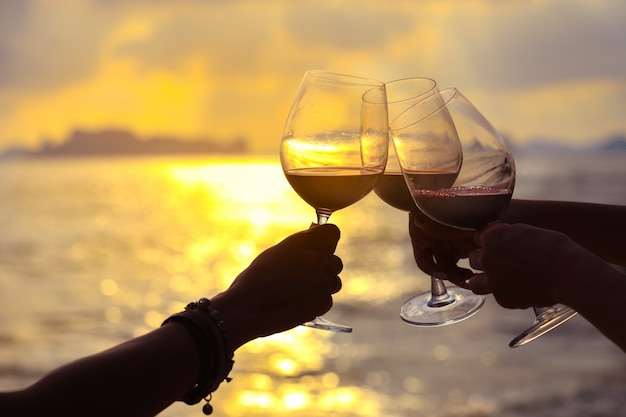 Close up on hands holding red wine glass on the beach during sunset Premium Photo