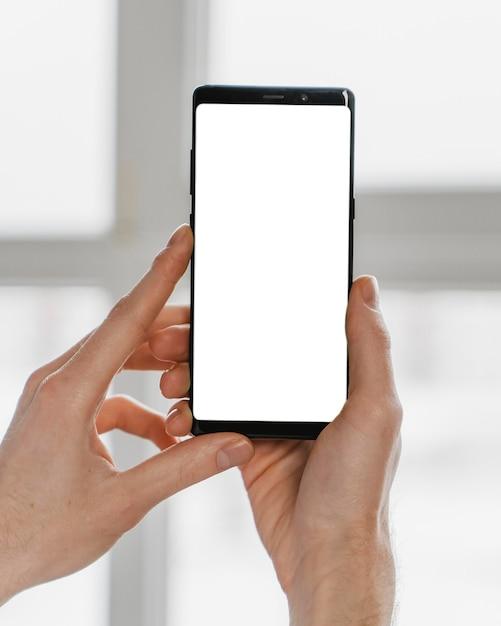 Mani del primo piano che tengono smartphone Foto Gratuite