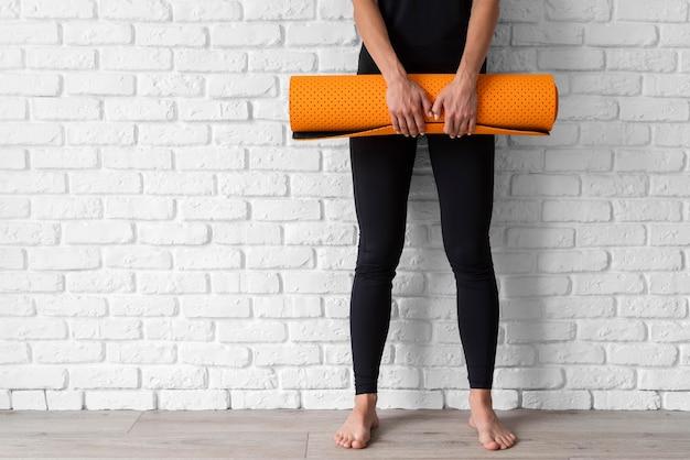 Mani del primo piano che tengono la stuoia di yoga Foto Gratuite