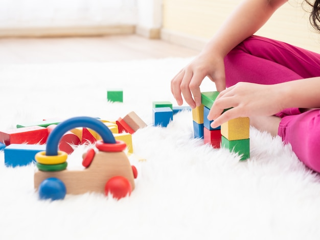 Close up hands of kid while playing wooden blocks on floor. Premium Photo