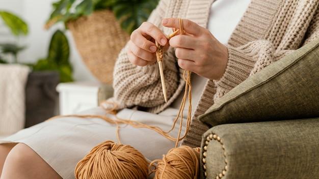 Mani del primo piano che lavorano a maglia con gli aghi Foto Gratuite