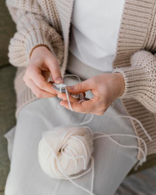 Mani del primo piano che lavorano a maglia con filato bianco Foto Gratuite