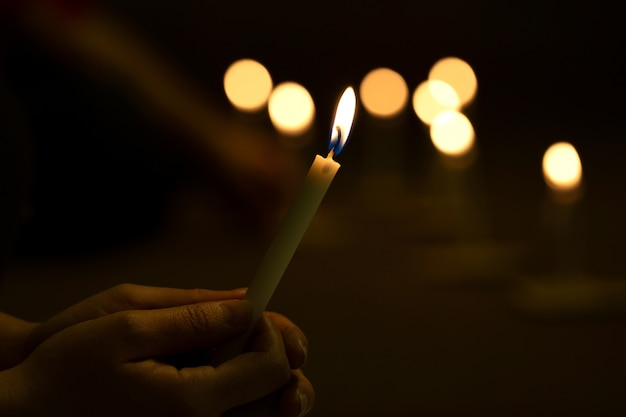 Close up hands  lighting candle vigil in darkness Premium Photo