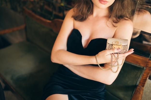 손에 작은 황금 지갑을 들고 검은 벨벳 드레스에 빈티지 카페에 앉아 우아한 아름다운 여성의 손을 닫습니다, 풍부한 세련된 아가씨, 우아한 패션 유행 액세서리 무료 사진