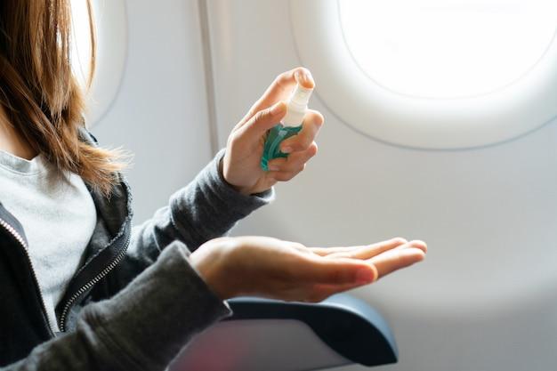 Закройте вверх руки женщины, распыления алкоголя из бутылки на ее руку на плоскости, защита от инфекционных вирусов, бактерий и микробов. концепция здравоохранения. Premium Фотографии