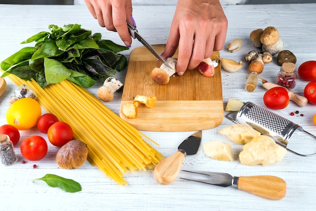 Close up hands only view of woman in apron cutting mushrooms, Premium Photo