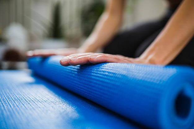 Close-up hands rolling up yoga mat Free Photo