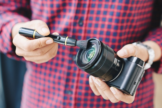 Close-up hands shot of professional photographer cleaning dust off camera lens with brush Free Photo