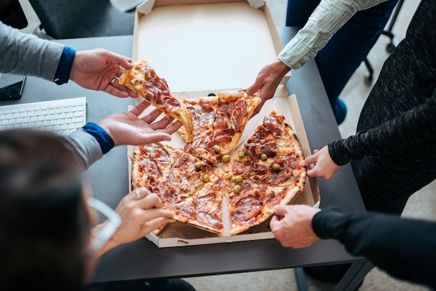 Close-up of a hands taking slices of pizza on a lunch break. Premium Photo