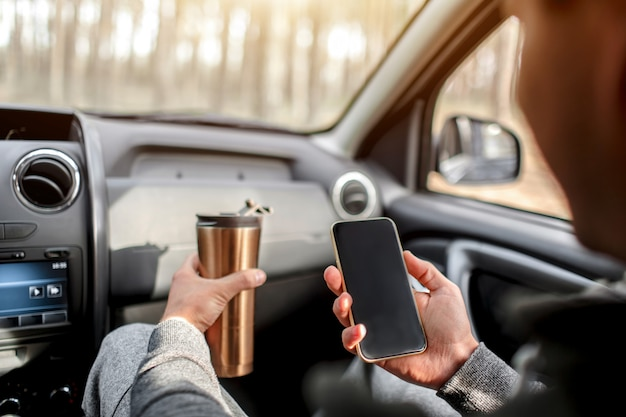Close-up of hands and thermos with smartphone in car. travel concept Premium Photo
