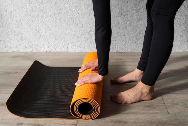Руки крупным планом касаются коврика для йоги Бесплатные Фотографии