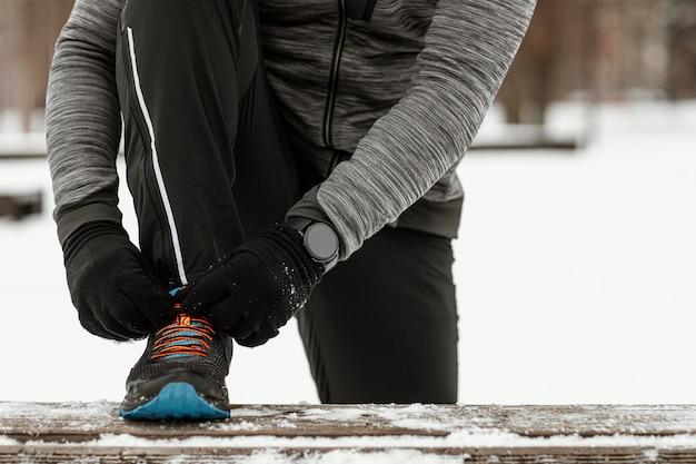 Mani del primo piano che legano i lacci delle scarpe Foto Gratuite