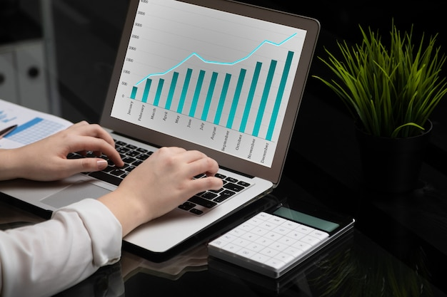 Close-up of hands typing on laptop with blank black screen next to charts and calculator Premium Photo