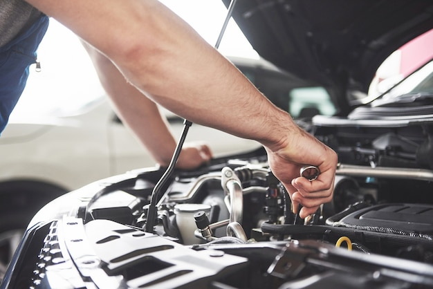Close up hands of unrecognizable mechanic doing car service and maintenance. Free Photo