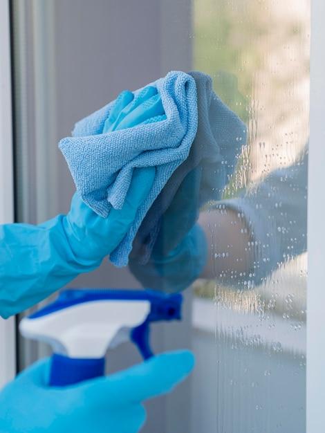 Макро руки в резиновых перчатках моют окна Premium Фотографии