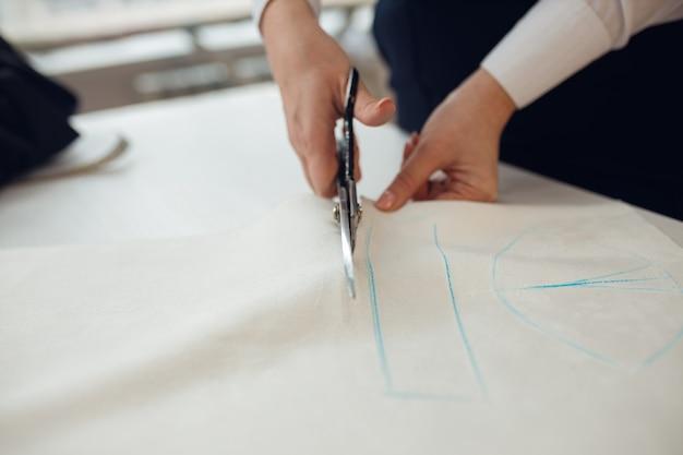 확대. Hands Woman 재단사 분필로 그녀가 만들고있는 의복 패턴을 표시 한 직물 롤 절단 작업. 프리미엄 사진