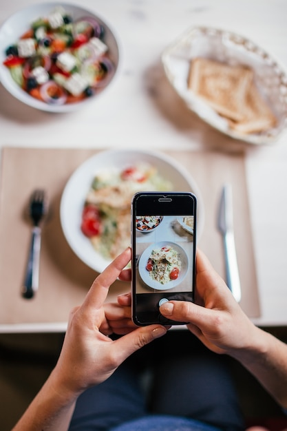 Close up hands of woman taking photo of fresh salad on the table with her phone. Premium Photo