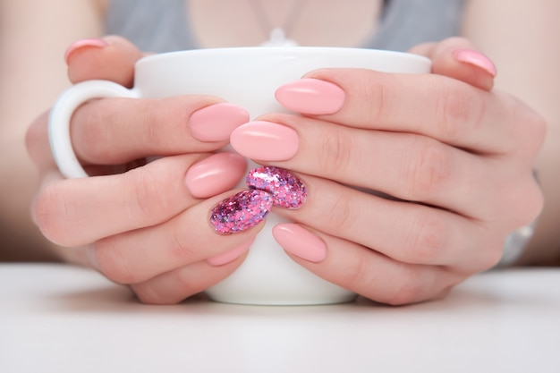 Close up hands of woman with pink manicure holding cup of coffee or tea. Premium Photo