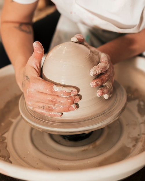 Close-up of hands working on pottery wheel Free Photo