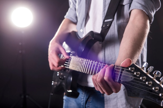 Close-up hands of young man is playing guitar. Premium Photo