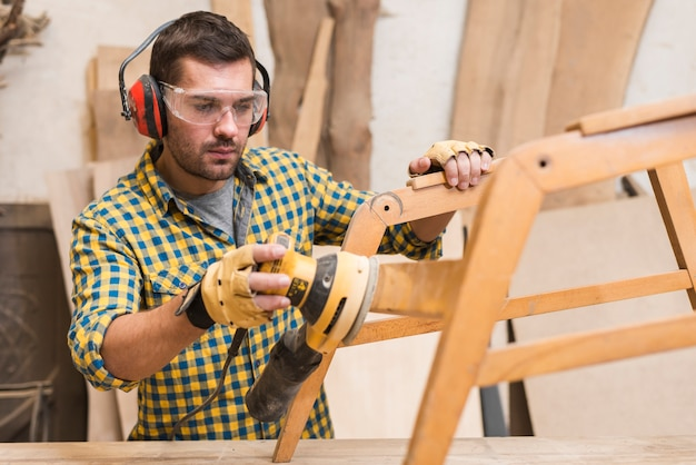 Close-up of a handyman sanding wooden furniture in workshop Free Photo