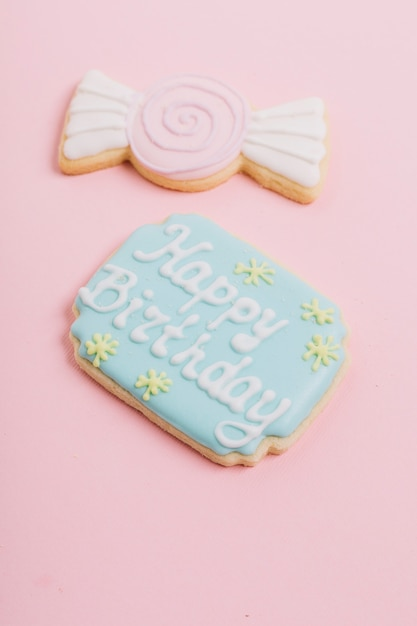 Close-up of happy birthday text on cookie over pink background Free Photo