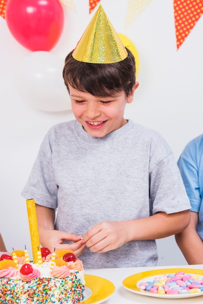 Close-up of a happy boy looking at colorful birthday cake Free Photo