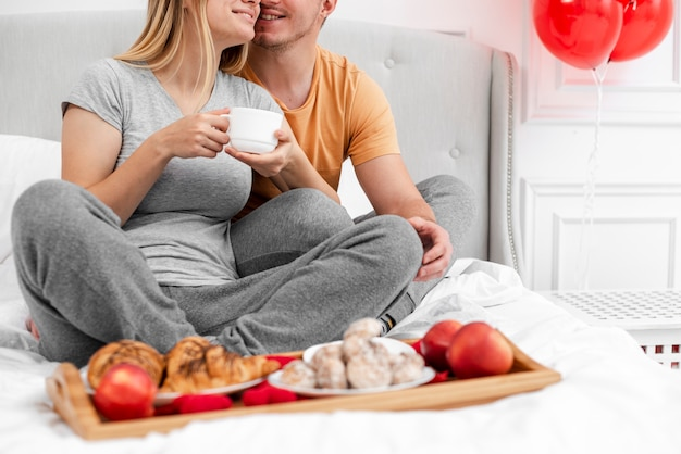Close-up happy couple with breakfast in bed Free Photo