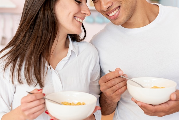 Close-up happy couple with cereals and milk Free Photo