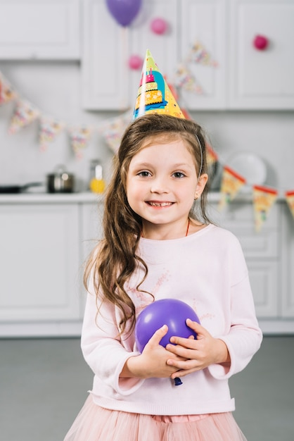 Close-up of a happy girl with purple balloon Free Photo