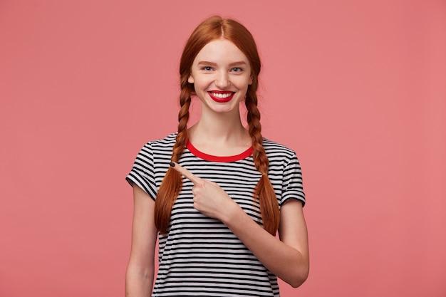 Primo piano di una ragazza adolescente dai capelli rossi ispirata felice mostra con il dito indice sul lato sinistro, è felice del prodotto, consiglia di prestare attenzione, mostra il posto per la tua pubblicità o testo promozionale Foto Gratuite