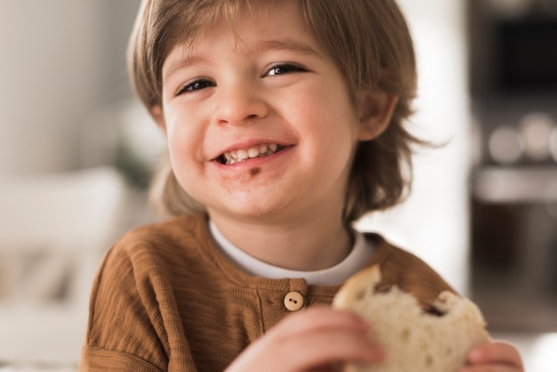 Close-up happy kid eating sandwich Free Photo