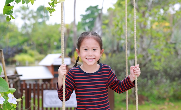 Close up happy little asian child girl play and sitting on the swing in the nature park. Premium Photo
