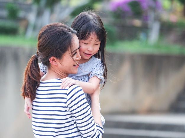 Close up happy little girl face in her mother arms. Premium Photo