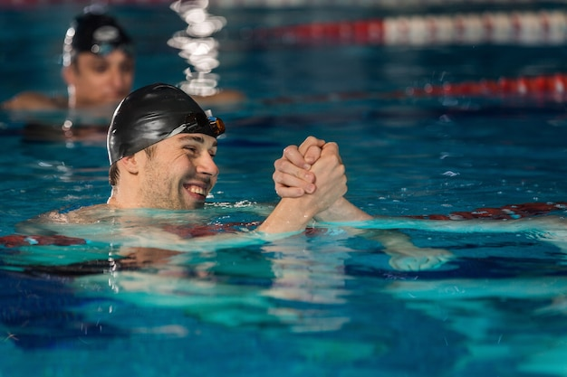 Close up of happy male swimmer shaking another swimmers hand Free Photo