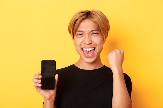 Primo piano del ragazzo asiatico felice che si rallegra che mostra lo schermo dello smartphone e dice sì, pompa a pugno come trionfante, vincere o raggiungere l'obiettivo, muro giallo Foto Gratuite