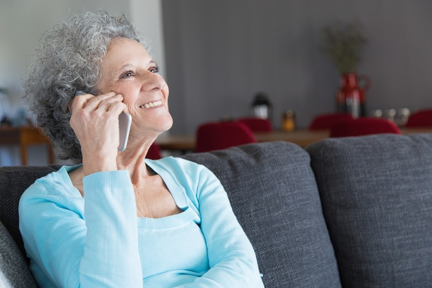 Close-up of happy senior woman talking on smartphone Free Photo