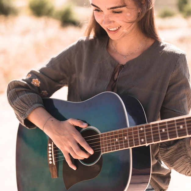Close-up of a happy teenage girl playing guitar Free Photo