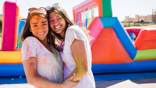 Close-up of a happy young women with holi color on their face embracing Free Photo