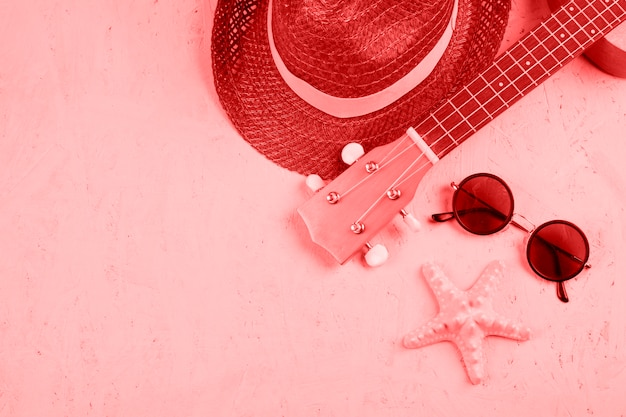 Close-up of hat; ukulele; sunglasses and starfish on coral textured background Free Photo
