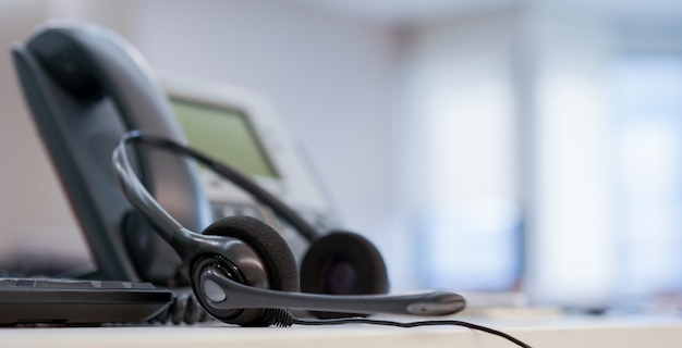 Close up on headset call center with telephone at office monitoring operation room concept Premium Photo