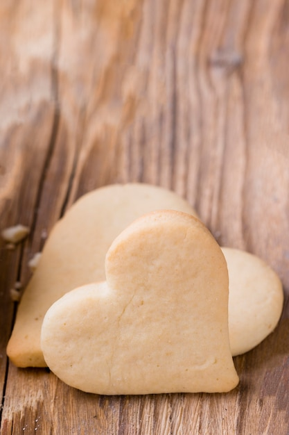 Close-up of heart-shaped cookies with wooden background Free Photo