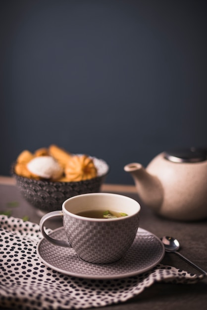 Close-up of herbal tea with bowl of cookies and teapot in background Free Photo