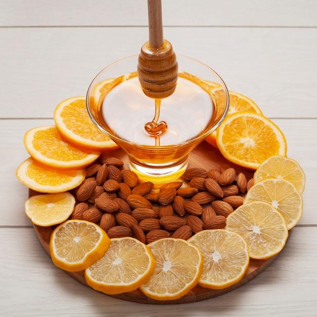 Close-up homemade honey surrounded by lemon slices Free Photo