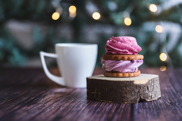 Close up of homemade pink and purple zephyr or marshmallow in powdered sugar with white mug on wooden with abstract bokeh . black currant, blueberry marshmallows. Premium Photo