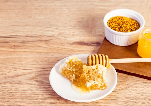 Close-up of honeycomb and bee pollen on wooden desk Free Photo