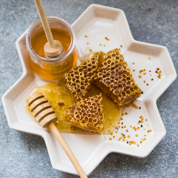 Close-up of honeycomb pieces with honey jar in tray Free Photo