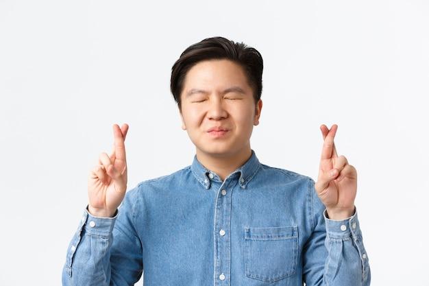 Primo piano dell'uomo asiatico preoccupato speranzoso chiudere gli occhi e incrociare le dita per buona fortuna, esprimere desideri, pregare in attesa di risultati, anticipare notizie, muro bianco in piedi Foto Gratuite